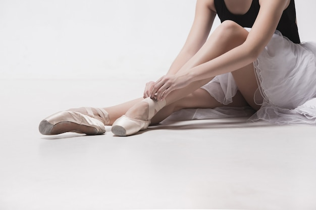 Ballerina dancer sitting down with her legs crossed on the white studio floor