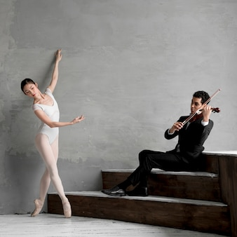 Балерина танцует и играет на скрипке музыканта