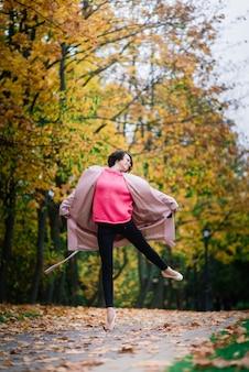 가을의 자연 속에서 춤추는 발레리나는 공정한 코트에 나뭇잎.
