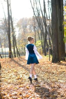 가을 사이 자연 속에서 춤추는 발레리나는 pointes에 나뭇잎.