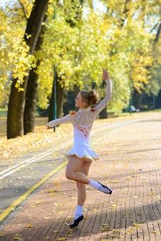 가을 단풍 사이 자연 공원에서 춤추는 발레리나.