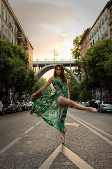 緑のドレスで通りで踊るバレリーナ
