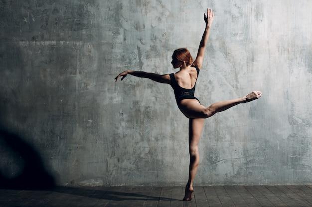 발레리나 여성. 젊은 아름 다운 여자 발레 댄서, 전문 복장, 포인트 신발 및 검은 시체를 입고.