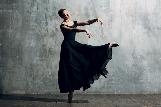 Ballerina female. young beautiful woman ballet dancer, dressed in professional outfit, pointe shoes and black dress.
