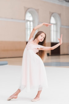 Ballerina girl in pink dress posing in dance studio