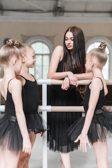 Ballerina girls with their instructor in dance studio