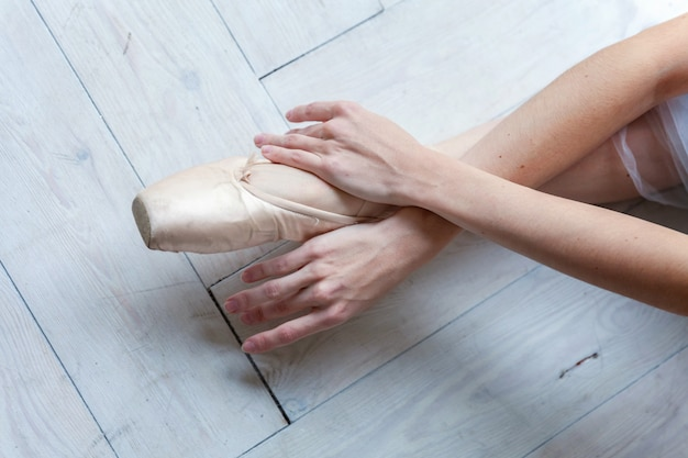 Ballerina hands puts pointe shoes on leg in dance class