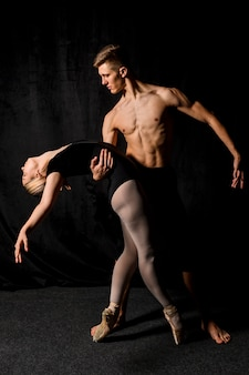 Ballerina held in pose by man