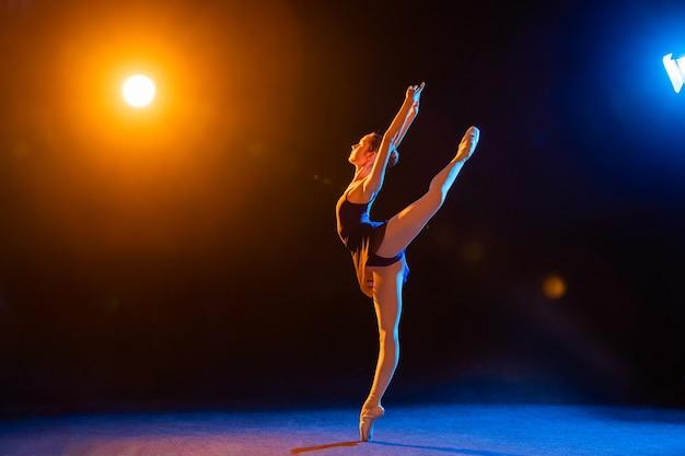검은 드레스를 입은 발레리나가 여러 가지 빛깔의 스포트라이트로 조명을 받아 춤을 추고 있습니다.