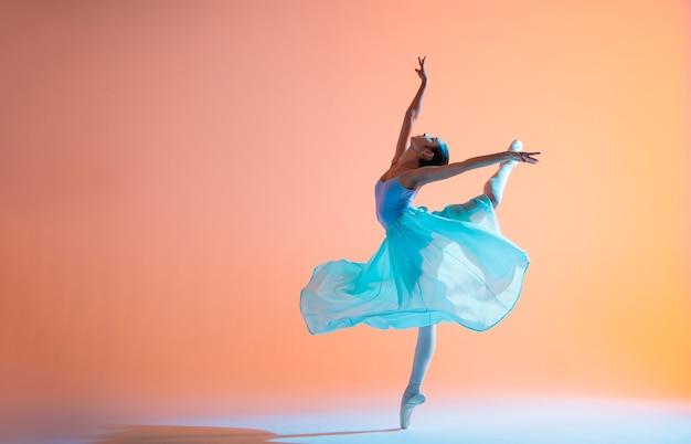 밝은 드레스를 입은 발레리나는 백라이트가있는 컬러 배경에서 춤을 추고 있습니다.