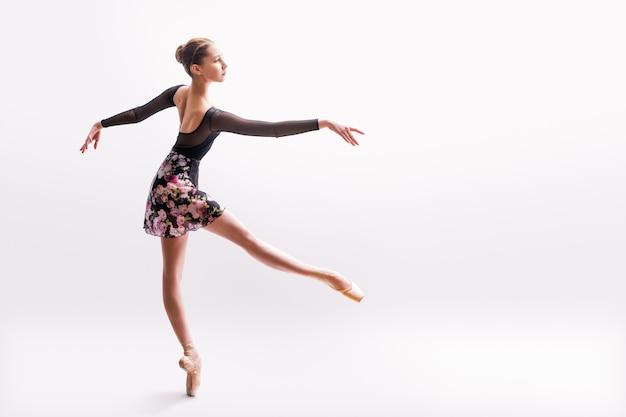 밝은 드레스를 입은 발레리나가 백라이트가있는 컬러 배경에서 춤을 추고 있습니다.