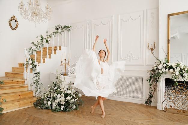 클래식 빈티지 홀에서 하얀 드레스를 입은 발레리나