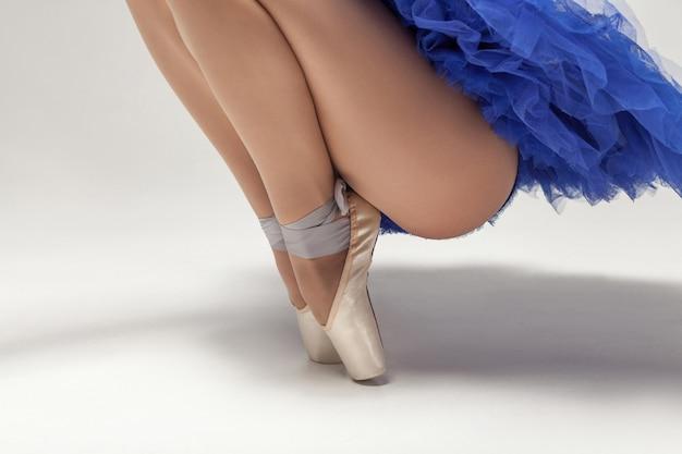 白い背景のクローズアップに分離されたトウシューズのつま先に立っている青いドレスのバレリーナ