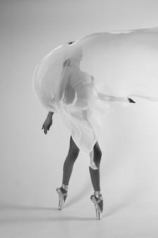 Балерина в теле на белой стене с летающей белой ткани. черно-белое видео.