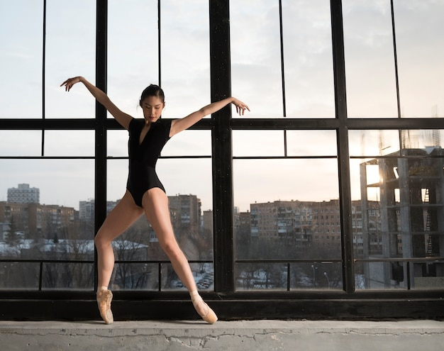 Балерина в купальнике танцует у окна