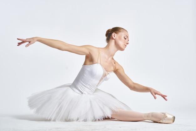 Балерина в пуантах у светлой стены
