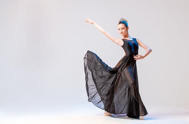 Pointe 신발의 발레리나와 흰 벽에 우아한 포즈로 포즈를 취하는 긴 검은 드레스