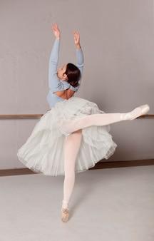 Балерина в юбке-пачке занимается балетом