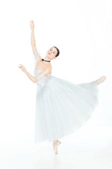 Балерина в белом платье позирует на пуанты, фон студии.
