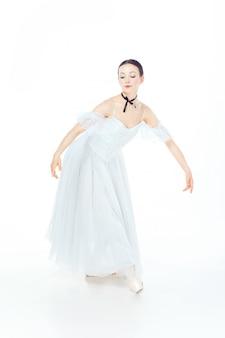 Балерина в белом платье позирует на пуанты, студия белая.