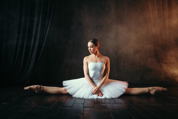 Балерина в белом платье сидит на шпагате, вид спереди. гибкость тела артиста классического балета