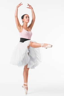 Ballerina in white tutu standing on tiptoe against white background