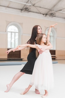 Ballerina instructor and girl poising in dance studio