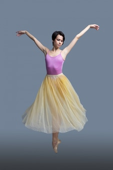 Ballerina is dancing on a gray