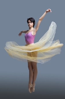 Ballerina is dancing in the studio on gray
