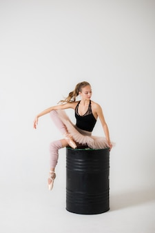Ballerina is sitting on a black barrel on a white background