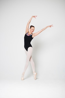 Ballerina is standing in a dancing pose on pointes on a white background
