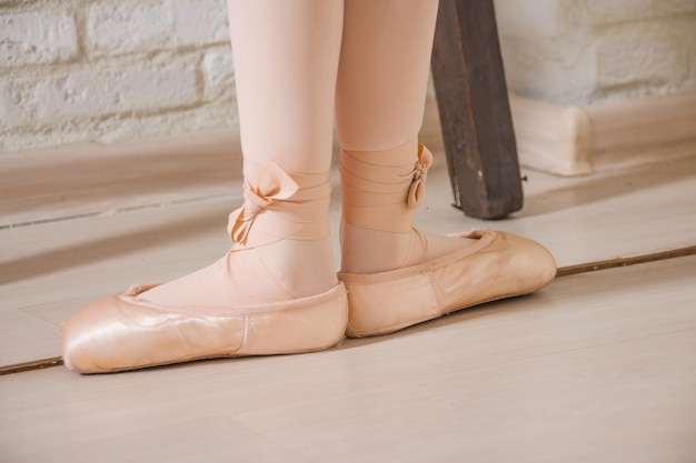 Ballerina legs first position in pointe, ballet dancer concept background.