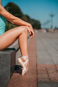 トウシューズのクローズアップでバレリーナの脚。バレリーナは街に座って休んでいます。
