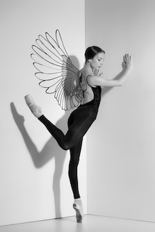 Ballerina like an angel posing on pointe shoes, studio gray background.