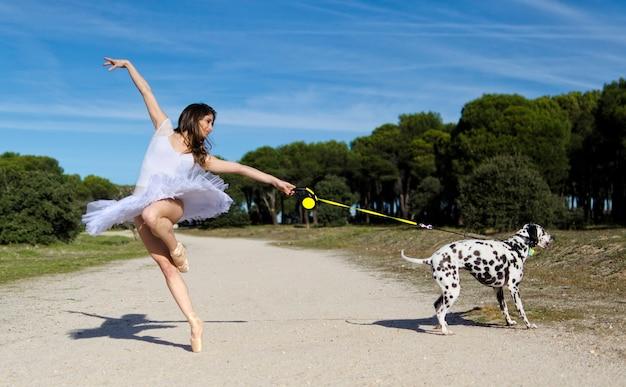 발레리나는 강아지와 함께 포즈를 취합니다.