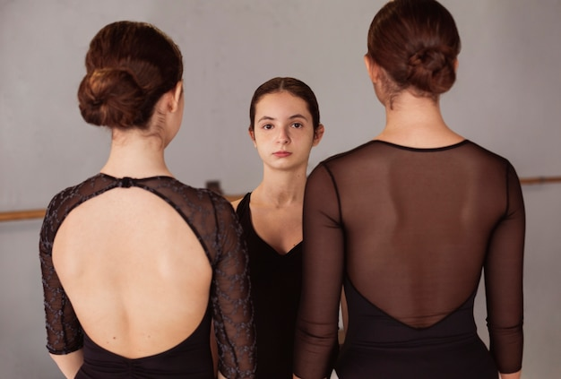 Ballerina posing against other two ballerinas turned around