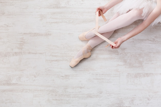 Ballerina puts on pointe ballet shoes