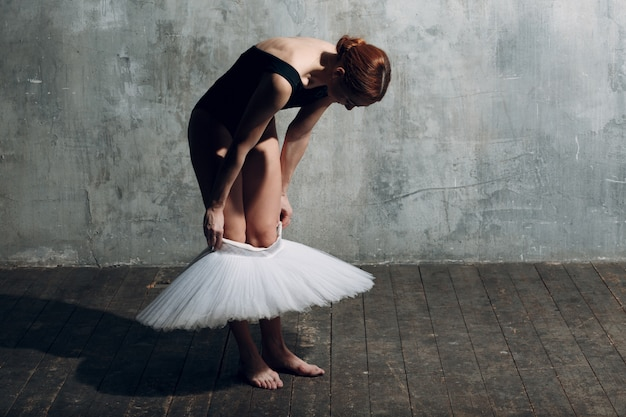 Балерина надевает белую пачку. молодая красивая балерина,