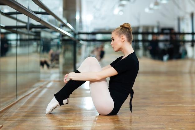 Ballerina resting on the floor in ballet class
