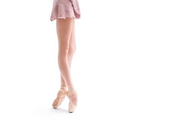 Ноги балерины в пуантах, стоя изолированные на белом фоне