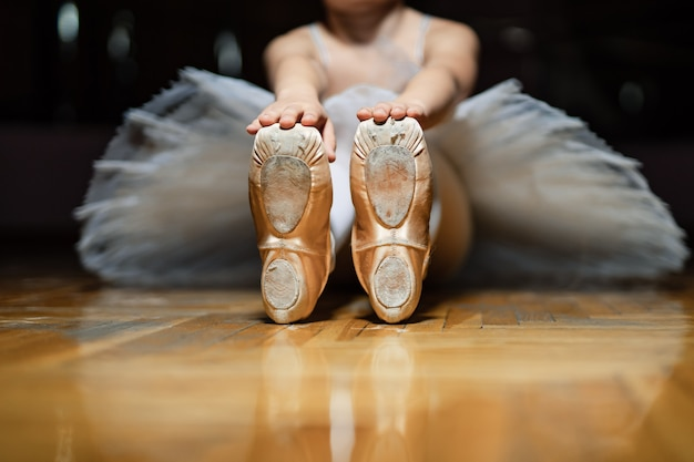Ballerina sitting on the floor of classroom and and holding for tiptoes of white ballet shoes on the wooden floor. classic ballerinas' pointes of a small girl . close-up