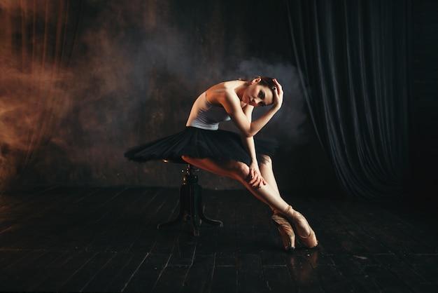 Балерина сидит на черной банкетке в театре