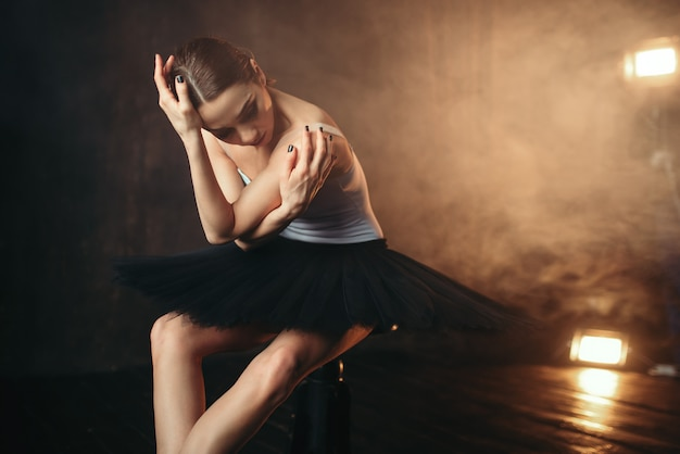 Балерина сидит на черной банкетке на сцене театра. элегантность балерины позирует в классе