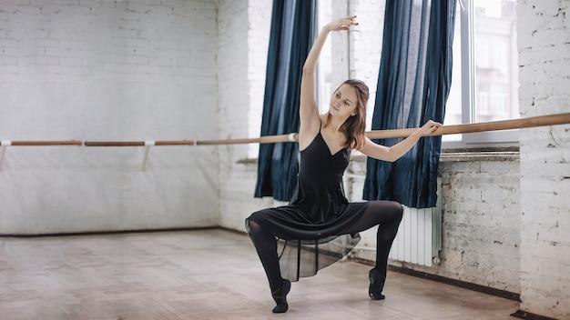 Ballerina squatting near barre