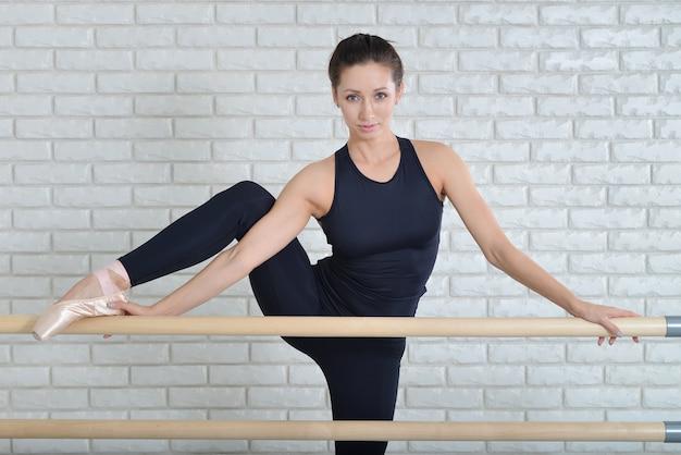 발레리나 발레 스튜디오에서 바레 근처에 자신을 뻗어, 아름다운 여자 댄서의 초상화를 닫습니다