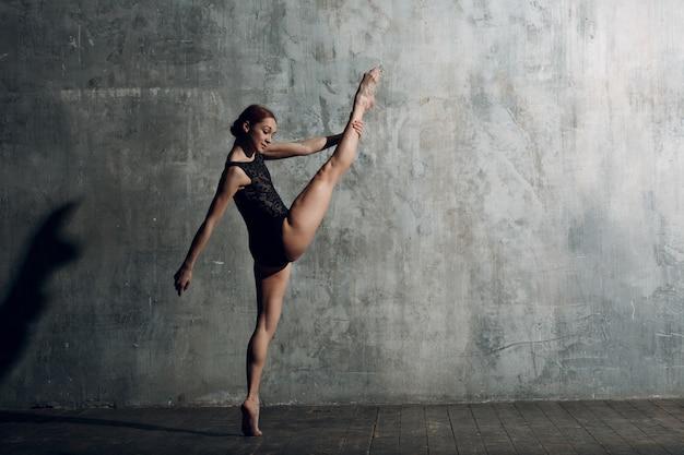 발레리나 스트레칭. 젊은 아름 다운 여자 발레 댄서, 전문 복장, 포인트 신발 및 검은 시체를 입고.
