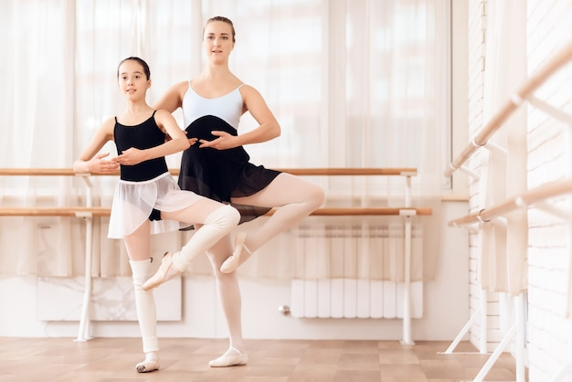 Ballerina teaches little girl at ballet school.