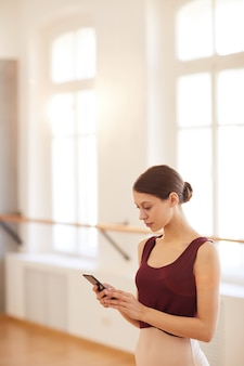 Ballerina texting sms in training studio
