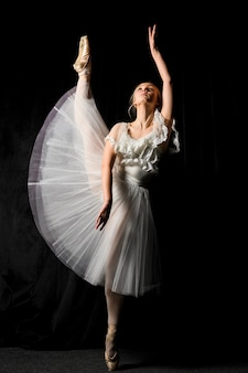 Ballerina in tutu dress posing with leg up