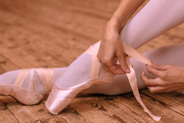 床に座ってポワントのリボンを結ぶバレリーナ